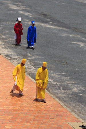 taoism: Tay Ninh, Vietnam - April 22, 2014: Priest going in a Caodai temple in Vietnam. Caodai is a Vietnamese religion mixing different religions from around the world, including Buddhism, Confucianism, Christianity, Hinduism, Islam, Judaism, Taoism, and Geniism Editorial