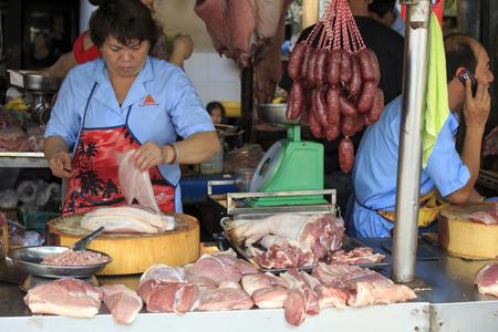 phen: Phnom Phen, Cambodia - April 21, 2014: vendor at the fresh meat market in the heart of Cambodia