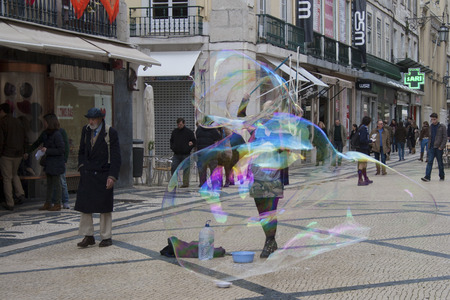 enclosing: LISBON, PORTUGAL - FEBRUARY 15 2014: Street performer blowing soap bubbles. A soap bubble is a very thin film of soapy water enclosing air that forms a hollow sphere with an iridescent surface Editorial