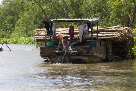 Le Binh, Vietnam - April 23, 2014: Man washing on a boat at the floating market, Vietnam. Stock Photo