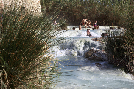 hydrothermal: Saturnia, Italy - November 17, 2013: Locals and tourists swim in the famous free hot springs in Saturnia. Saturnia is a spa town in the municipality in Manciano in the Tuscan Maremma, Italy. Editorial