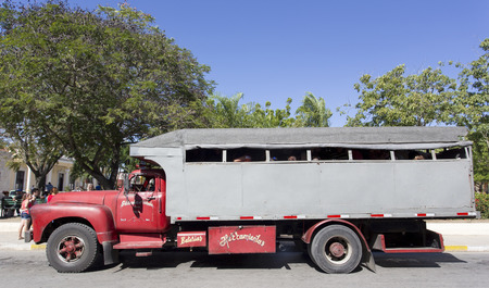 HOLGUIN, CUBA - DECEMBER 28, 2015: People ride truck buses (camion) in Holguin. Due to embargo Cuba had problems acquiring normal buses Stock Photo - 59008781
