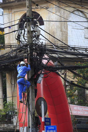 phen: Phnom Phen, Cambodia - April 21, 2014: man working at tangled wires on electric poles in Cambodia