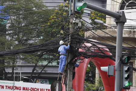 phnom phen: Phnom Phen, Cambodia - April 21, 2014: man working at tangled wires on electric poles in Cambodia