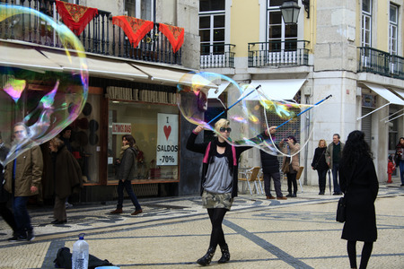 enclosing: Lisbon, Portugal - February 15, 2014: Street performer blowing soap bubbles. A soap bubble is a very thin film of soapy water enclosing air that forms a hollow sphere with an iridescent surface