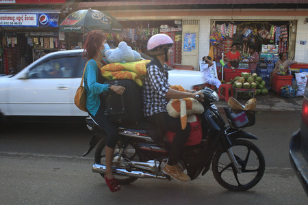 phnom penh: Phnom Penh, Cambodia - May 1, 2013: Skillful motorbike driver with a big stack of luggage on the streets of Phnom Penh, Cambodia Editorial