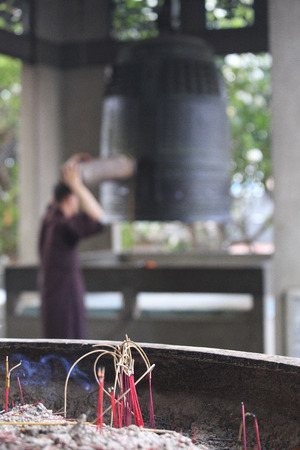phnom phen: Phnom Phen, Cambodia - April 21, 2014: an out of focus monk is ringing a bell. Focus on religious incense burning Stock Photo