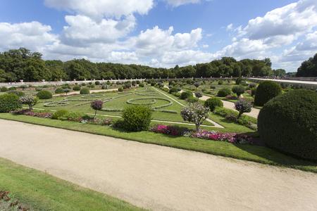 Chenonceaux, France - August 09, 2016: Chateau de Chenonceau royal medieval french castle. Garden with walking tourists