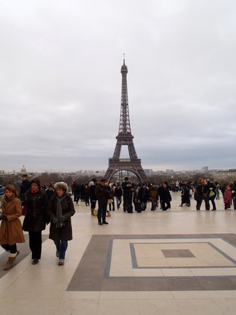 Paris, France - December 09, 2012: Tourists taking picture in front of Eiffel Tower on the background