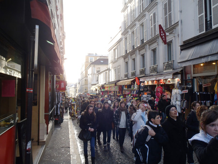 Paris, France - December 15, 2012: Tourists walking down a typical street with cafes and restaurants.