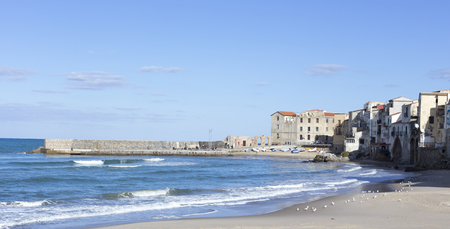 Cefalu, Italy - January 02, 2015: empty beach of Cefalu leading to its old town in a sunny winter day, Sicily Stock Photo
