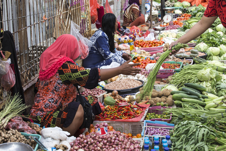Labuanbajo, Indonesia - August 17, 2015: Unidentified group of women wearing hijab and traditional clothings selling tropical fruit in the street Editorial