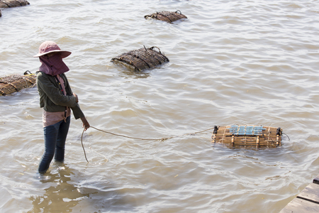 Kep, Cambodia - April 26, 2014:  Traditional asian fishing. Cambodian men on the fishing boat pass the catch of blue crabs to woman for sale