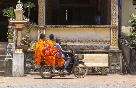 Sihanoukville, Cambodia - April 26, 2014: three young monks riding a motorbike in front of a temple in Sihanoukville, Cambodia