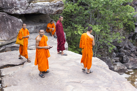 Popokvil Waterfall, Kep, Cambodia - April 27, 2014: Monks visiting Kep waterfall near Kep in Cambodia. The falls lie at the edge of the highland march which covers much of the mountain-top Editorial