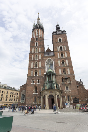 Krakow, Poland - April 25, 2017: Saint Marys Basilica in Rynek Glowny (main square) Krakow, Poland. Tourists walking in the square in front of the church