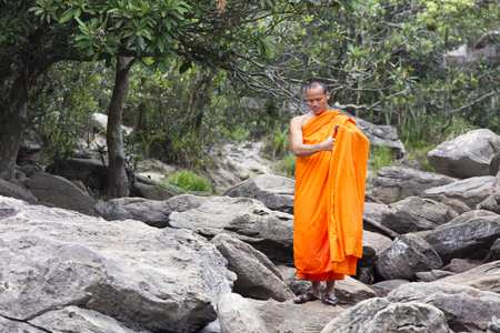 Popokvil Waterfall, Kep, Cambodia - April 27, 2014: Monk visiting Kep waterfall near Kep in Cambodia. The falls lie at the edge of the highland march which covers much of the mountain-top