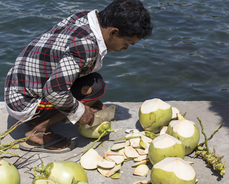 cutting: Sihanoukville, Cambodia - April 30, 2014: An unidentified man cutting and selling coconuts close to the sea