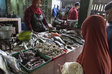 Yogyacarta, Indonesia - August 04, 2017: fish at the market; unidentified woman is selling fishes Редакционное