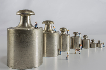 weights for balance of various sizes in a row with miniature workers Stock Photo