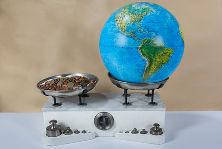 Balance with two metal plates with weights,  coins and the planet earth