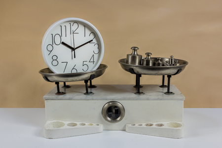 Balance with two metal plates with weights and clock