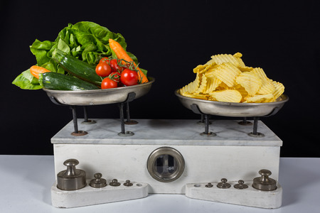Balance with two metal plates with weights, vegetable and chips Stock Photo