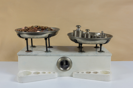 kilograms: Balance with two metal plates with weights and coins Stock Photo