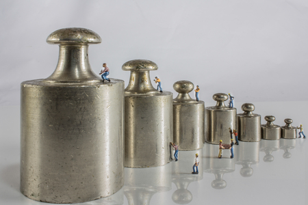 standard steel: weights for balance of various sizes in a row with miniature workers Stock Photo