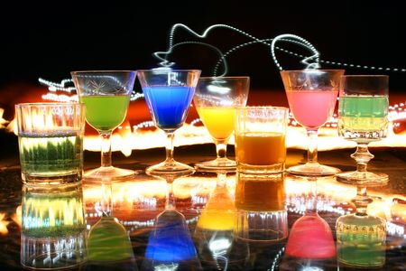 Some backlit glasses with colored liquids in them, very colorful composition
