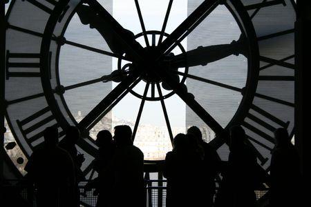 backlit: Retroiluminada las personas con gran reloj en el fondo