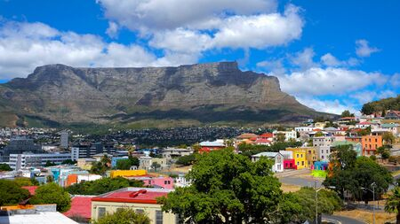 Beautiful view from Bo-Kaap or Malay at sunny day with Table Mountain on background. The city of Cape Town is a famous travel destinationin Africa. Vivid colors filtered. February 2020 Stock Photo
