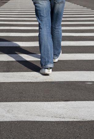 mans legs crossing the street