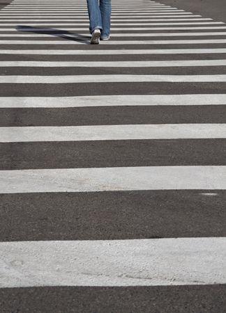 crossing legs: mans legs crossing the street