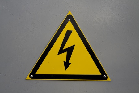 Yellow electricity warning sign on gray background Stock Photo - 9216204
