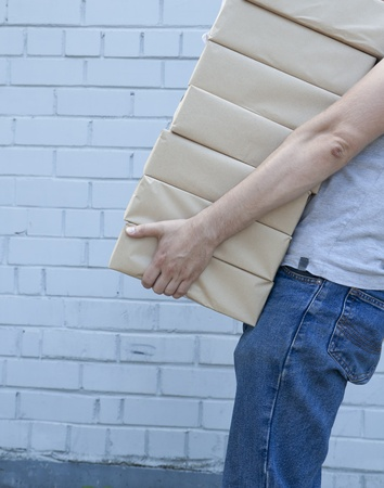 carrying box: man holding a pile of package parcels