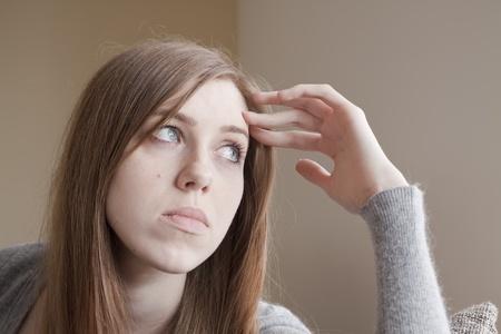 pensiveness: Triste giovane donna seduta sul letto Archivio Fotografico
