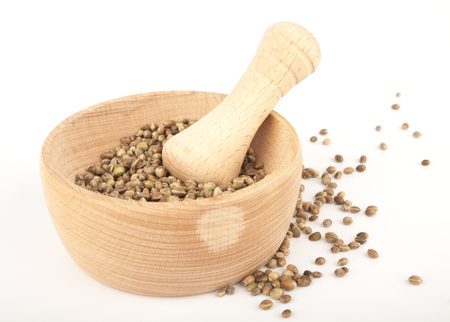 spicery: Hemp seed in wooden pounder isolated on white