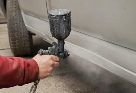 Hand holding spray paint gun photo
