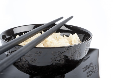 Boiled rice in a ceramic bowl and chopsticks isolated on white photo