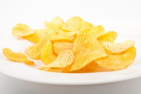 tentempi�: Las papas fritas tirado en el plato blanco Foto de archivo