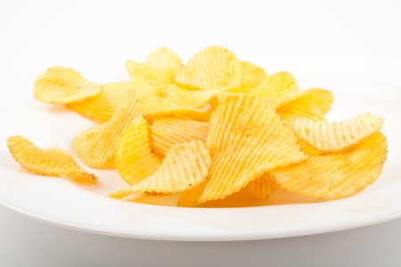 Potato chips heap on the white plate photo