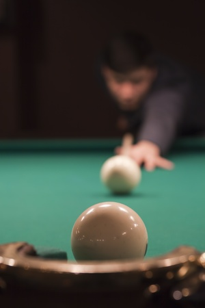 Hand holding billiard cue aimed at a white ball photo