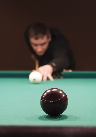 Hand holding billiard cue aimed at a black ball