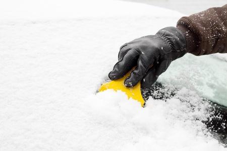 Grattage neige et la glace du pare-brise de voiture Banque d'images