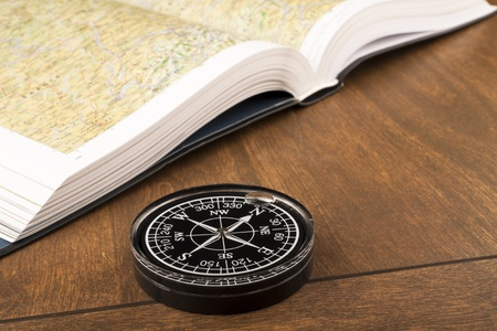 guidebook: Compass and atlas book on the wooden table