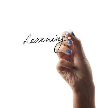 Hand writing the word LEARNING isolated on white background photo