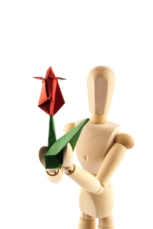 Greetings. Wooden mannequin giving handmade paper flower photo