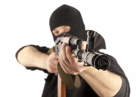 Man in mask with gun on white background