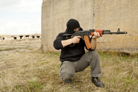 Warrior in mask with gun photo